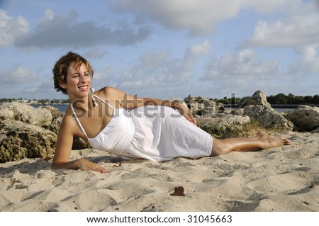 pretty woman in white dress, in the sand at the beach - stock photo