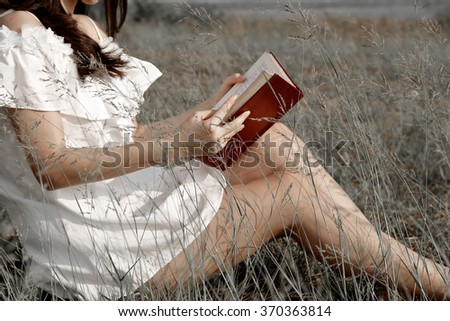 Pretty woman in white dress sit and reading a book in grass field under mild warm evening sun light - stock photo