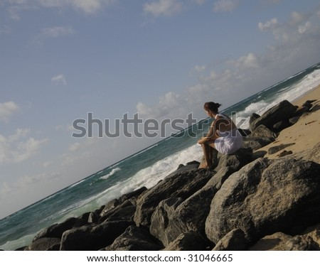 Pretty woman in white dress sitting on rocks watching the ocean - stock photo