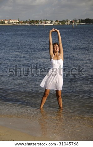 Pretty woman in white dress stretching at the beach - stock photo