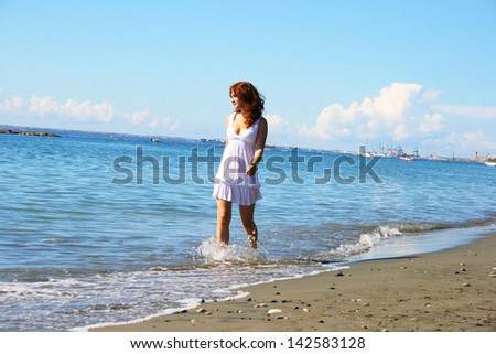 Pretty woman in white dress walking on the beach.