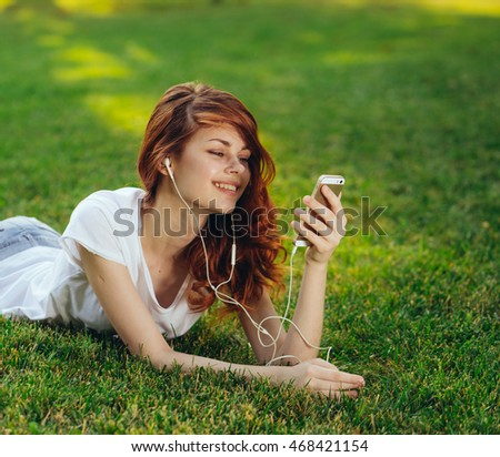 Pretty woman in white with the phone on the grass