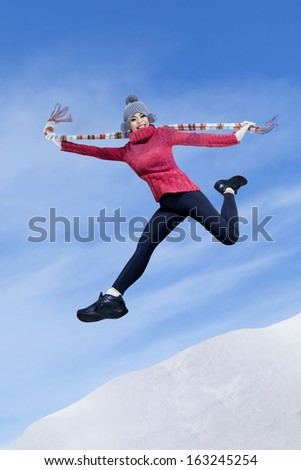 Pretty woman in wintertime jumping on the snowy mountain - stock photo