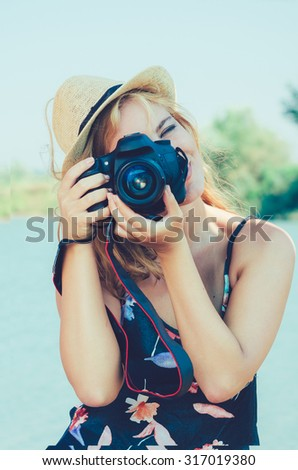 Pretty woman is a professional photographer with dslr camera / photography of young Caucasian woman outdoors. Vintage Instagram style effect, shallow DOF, grain texture visible on maximum size. - stock photo