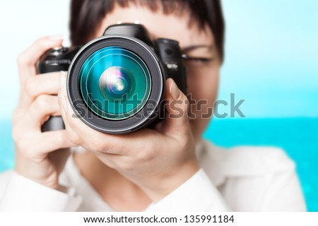 Pretty woman is a professional photographer with slr camera - stock photo