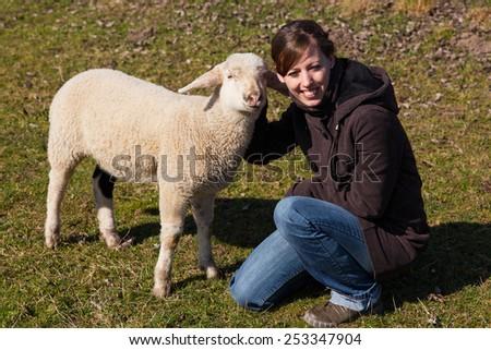 pretty woman is kneeling beside a small lamb - stock photo