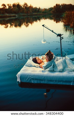 Pretty woman is laying on the floating bed with a book and toy. Summer sunset on the background.
