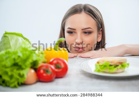 Pretty woman is making decision to eat vegetables. She is looking at it and does not pay her attention on hamburger. Isolated on a white background - stock photo