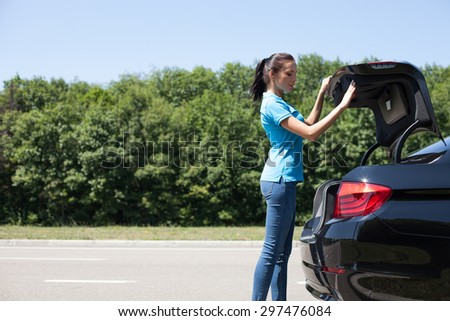 Pretty woman is opening the car trunk. She is looking inside with interest. Copy space in left side