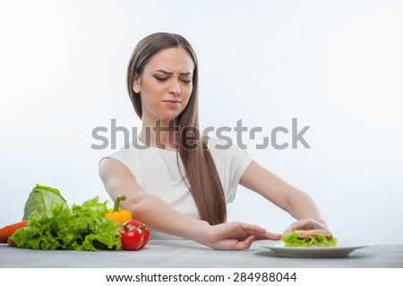 Pretty woman is refusing to eat unhealthy hamburger. She is looking at it with disgust. Isolated on a white background - stock photo