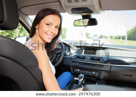 Pretty woman is sitting at steering wheel of her car. She is looking back and smiling - stock photo