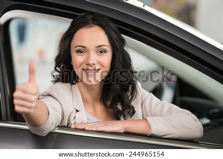 Pretty woman is sitting in a new car and looking at the camera. - stock photo