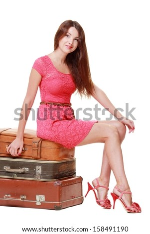 Pretty woman is sitting on old leather case on Beauty and Fashion
