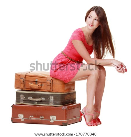 Pretty woman is sitting on old leather case on Beauty and Fashion - stock photo