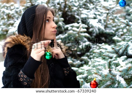 Pretty woman is standing beside a fir tree, smiles happy and holds a glass ball in her hand.