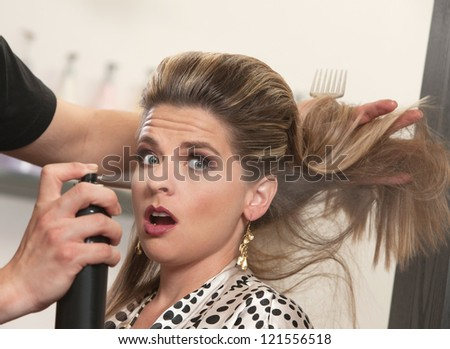 Pretty woman is startled by stylist using hair spray - stock photo