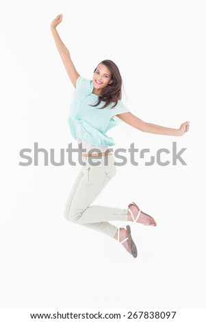 Pretty woman jumping looking at camera on white background