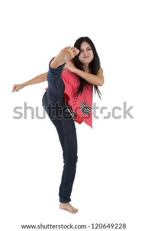 pretty woman kicking with her foot high up, isolated on white background