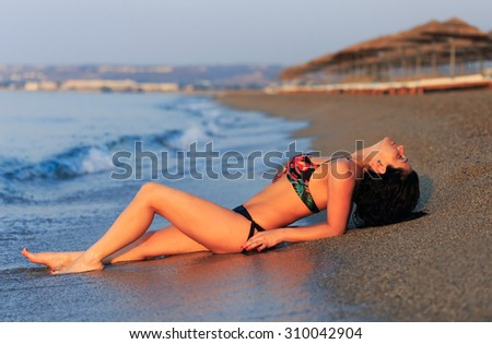Pretty woman laying on wet sand at the beach in the morning. - stock photo