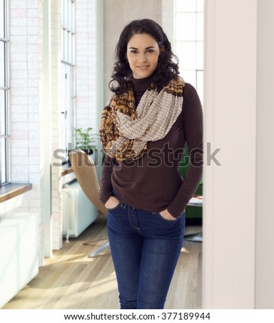 Pretty woman leaning against wall at home, smiling, looking at camera. - stock photo