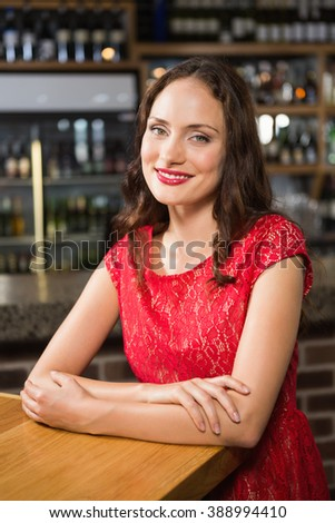 Pretty woman leaning on a wooden table in a pub