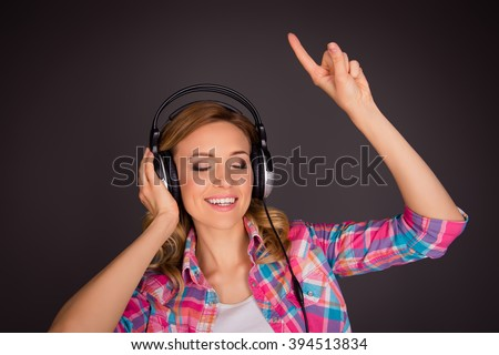 Pretty woman listening music and gesturing with raised hand