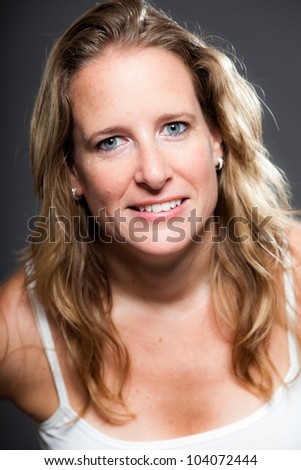 Pretty woman long blond hair wearing light white shirt. Isolated on grey background. Studio shot.