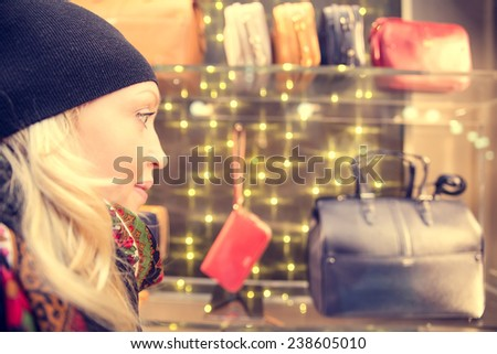 Pretty woman looking at decorated shop window - Young girl thinking about which bags to buy  - stock photo