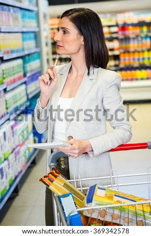 Pretty woman looking at product on shelf and holding grocery list in supermarket