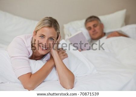 Pretty woman looking at the camera while her husband is sleeping - stock photo