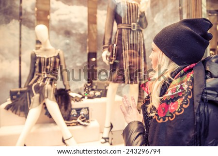 Pretty woman looking at window shop - Sale in clothes shop - stock photo