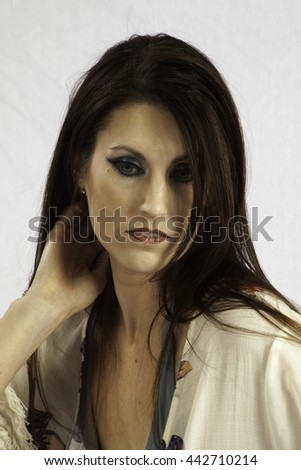 Pretty woman   looking thoughtful   with her hand in her hair - stock photo