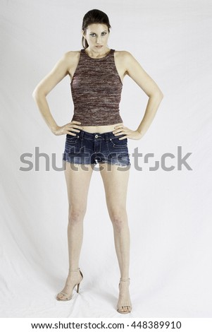 Pretty woman looking thoughtfully in shorts and her hands on her hips - stock photo
