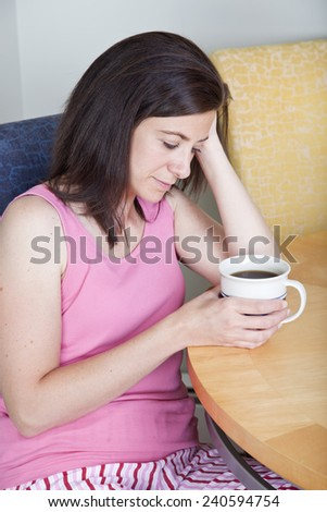 Pretty woman looking unhappy with mug at home - stock photo