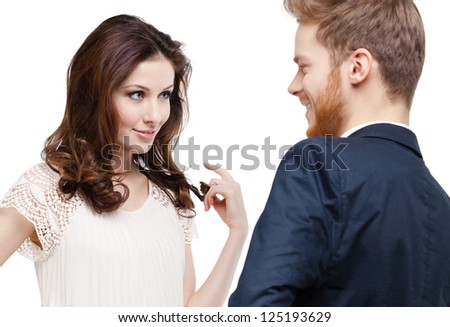 Pretty woman looks slily at her boyfriend and touches her hair, isolated on white