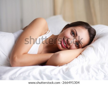 Pretty woman lying  in bed - stock photo