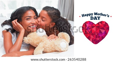 Pretty woman lying on bed with her daughter kissing cheek against happy mothers day - stock photo