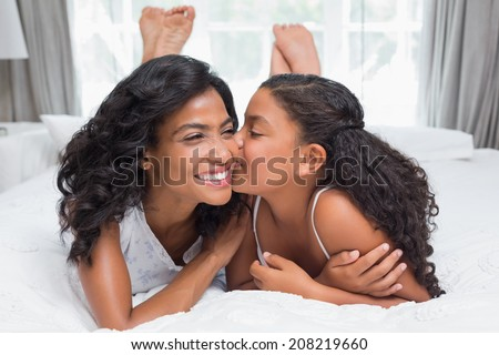 Pretty woman lying on bed with her daughter kissing cheek at home in bedroom - stock photo