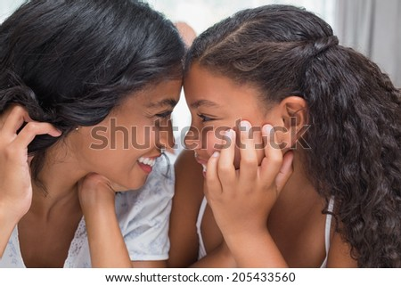 Pretty woman lying on bed with her daughter smiling at each other at home in bedroom - stock photo