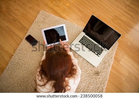Pretty woman lying on floor using technology at Chritmas at home in the living room - stock photo