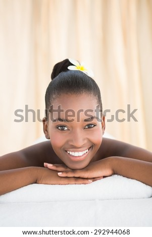Pretty woman lying on massage table smiling at the camera at the health spa - stock photo