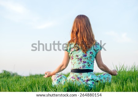 Pretty woman meditate sitting on the grass - stock photo