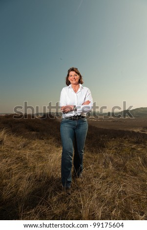 Pretty woman middle aged enjoying outdoors. Standing in grassy dune landscape. Clear sunny spring day with blue sky. - stock photo