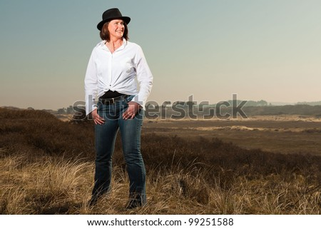 Pretty woman middle aged with a hat enjoying outdoors. Clear sunny spring day with blue sky. - stock photo