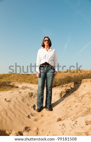 Pretty woman middle aged with sunglasses enjoying outdoors. Clear sunny spring day with blue sky. - stock photo