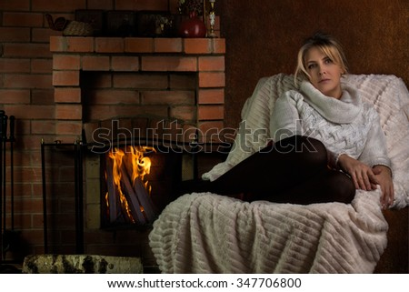 Pretty woman near fireplace
