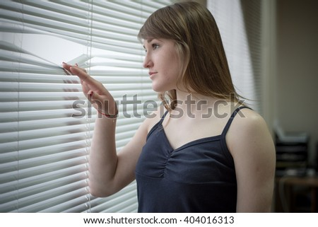 Pretty woman near window looking through the blinds