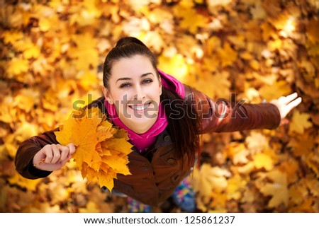 pretty woman on a background of autumn leafs. top view