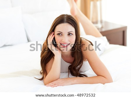 Pretty woman on phone lying on bed at home - stock photo