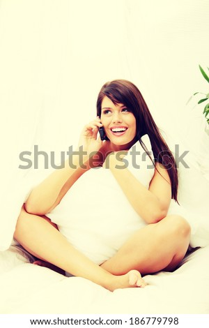 Pretty woman on phone siting on bed at home